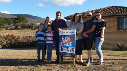 family with sold sale sign